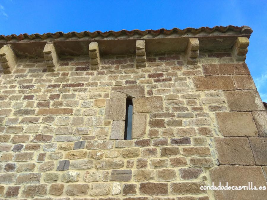 Detalle del muro sur de la nave de Santa Leocadia de Helguera con modillones y aspillera