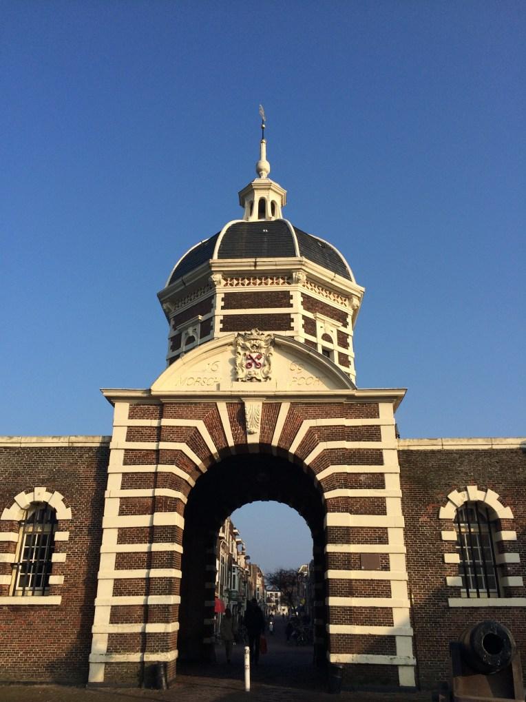 "Gerbang Leiden sebelah barat. Lambang dari Leiden adalah dua kunci merah yang saling menyilang dengan latar belakang putih. Leiden disebut sebagai ""Sleutelstad"" (""kota kunci"")"