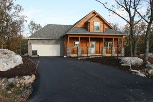 custom log house with garage and stone
