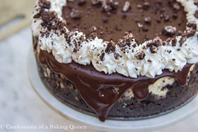 oreo cheesecake showing chocolate ganche drip on a cake stand