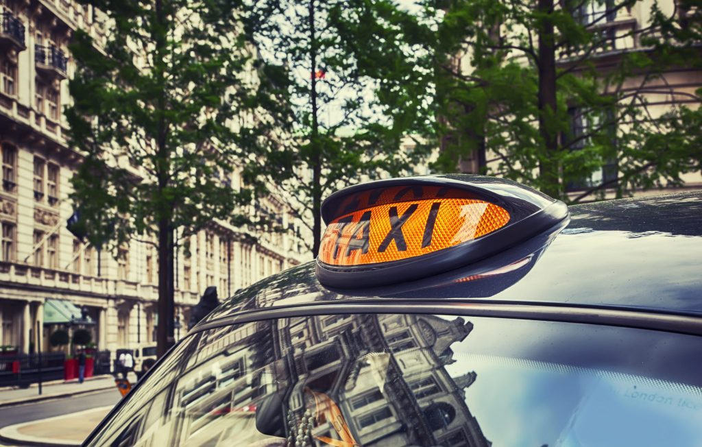 A black cab in a London street; the angle is looking at the orange taxi sign mounted on the roof, whilst trees and buildings are visible in the background.