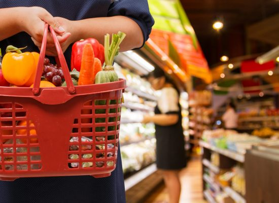 A shopper stands in the foreground of the picture holding a basket of vegetables and fruit, meanwhile in the background is an out of focus grocery store.