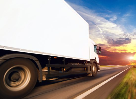 A white lorry driving along a straight flat road, beneath a beautiful sunset. The terrain is out of focus as a result of motion blur.