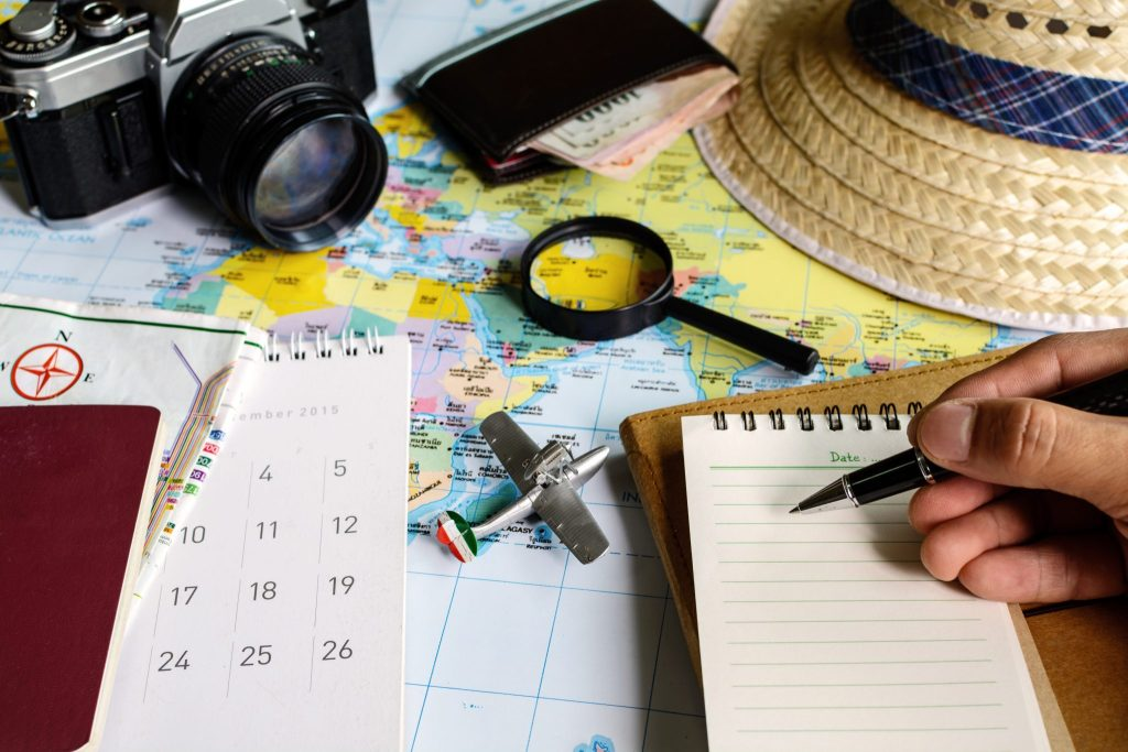 A collection of travel paraphernalia such as a map, straw hat. magnifying class, calendar, camera, wallet with money and a small aeroplane model. In the bottom right corner, a hand holds a pen, poised to write on a small notebook.