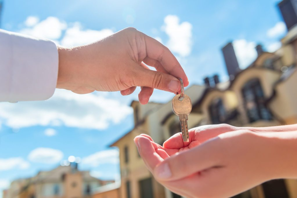 Against the blurred backdrop of some newly build houses, a hand is passing a door key to someone else.