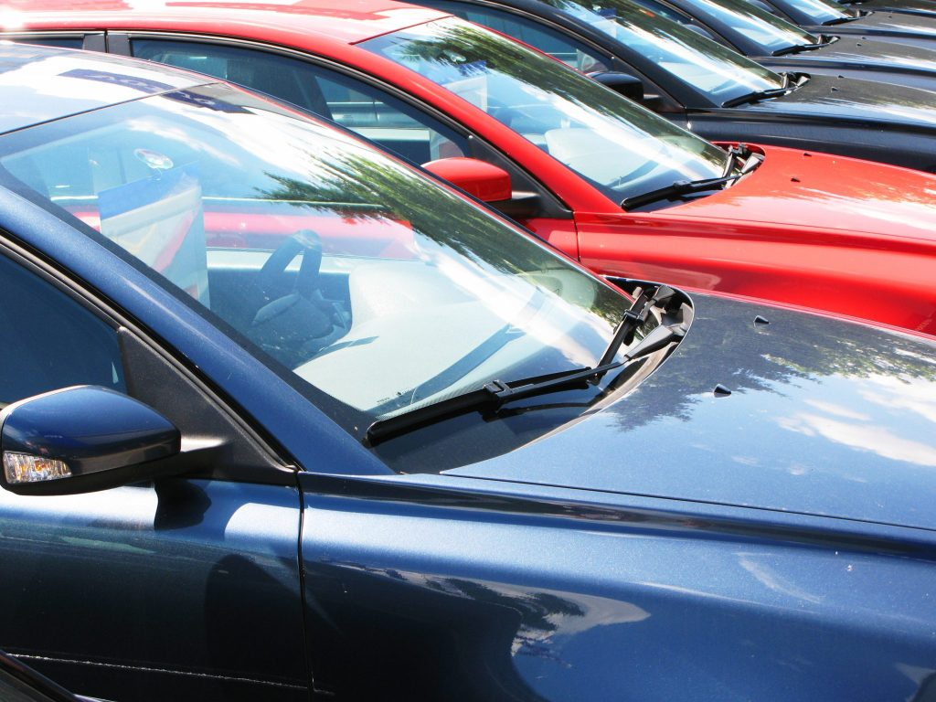 A row of blue and red cars on a carpark of forecourt; the camera angle is looking across the windscreens where you can see their is pricing information on display.