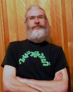 Image of the author, arms folded, in a black tshirt.