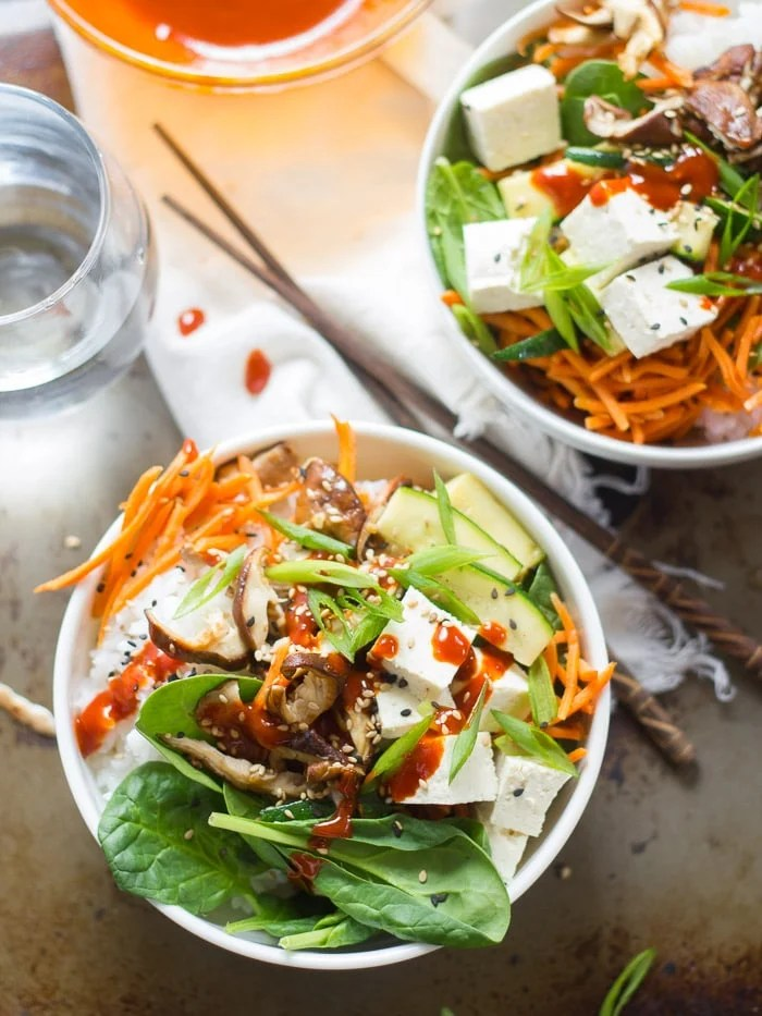 Two Bowls of Vegan Bibimbap on a Rustic Surface with Water Glass and Chopsticks