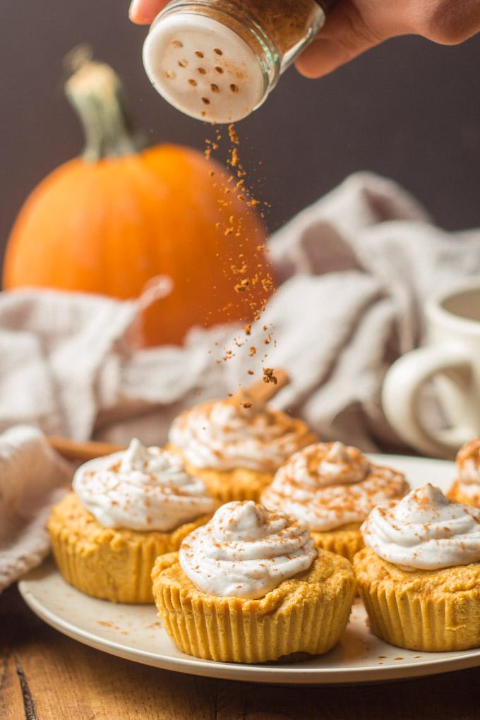 Hand Sprinkling Cinnamon Over a Plate of Mini Vegan Pumpkin Cheesecakes