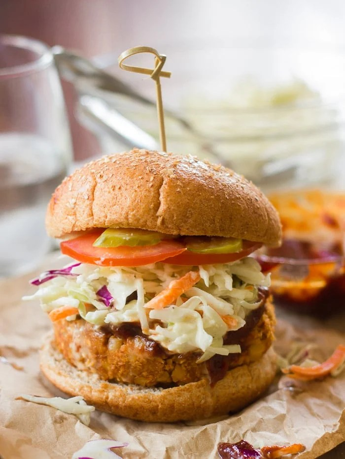 Barbecue Chickpea Burger on a Bun Topped with Slaw Barbecue Sauce and Tomato Slices with Glass Bowl and Drinking Glass in the Background