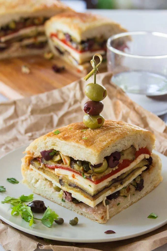 Vegan Muffaletta Slice on a Plate with Drinking Glass and Cutting Board in the Background