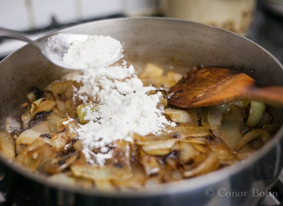 Cook the flour in the onions for a little bit.