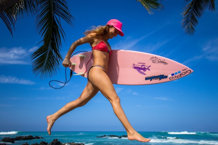 Alison never travels without her pink sustainable surfboard from E-Tech. Photo Credit: Sarah Lee