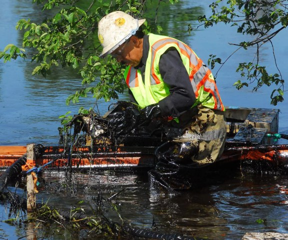 A worker lifts bitumen-covered debris from the Kalamazoo River