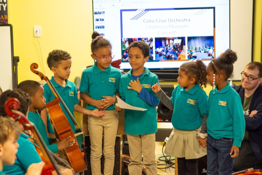 Image of students wearing teal shirts with logo at a school event. Some students are presenting work, and others have cellos.