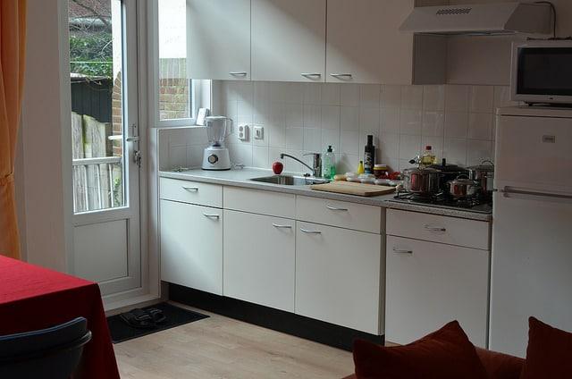 aménagement d'une petite cuisine blanche donnant sur une petite salle à manger