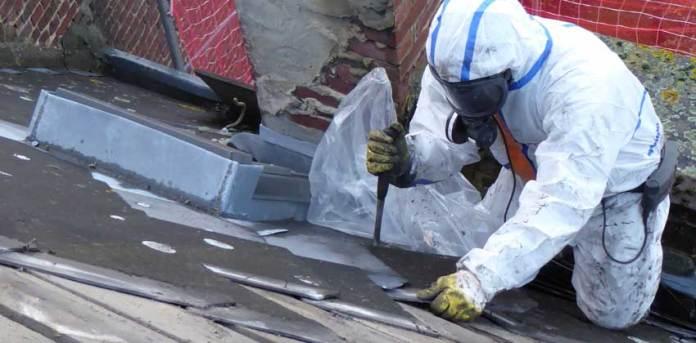 Un expert de l'amiante retire les tuiles d'amiante