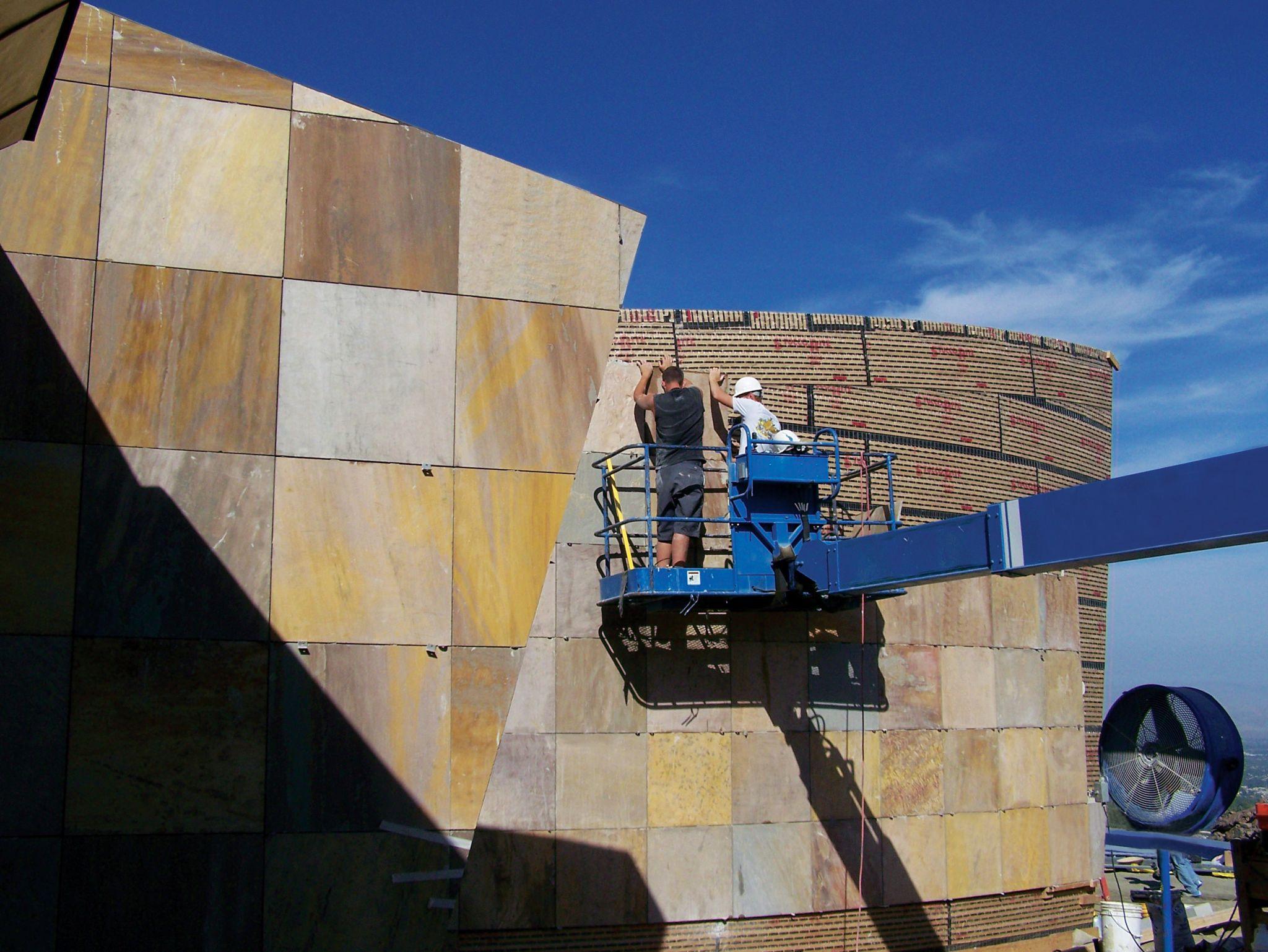 Bu işçiler, kum taşını bir binanın dış duvarına metal açılı klipslerle mekanik olarak sabitlemek için bir manlift kullanıyor.