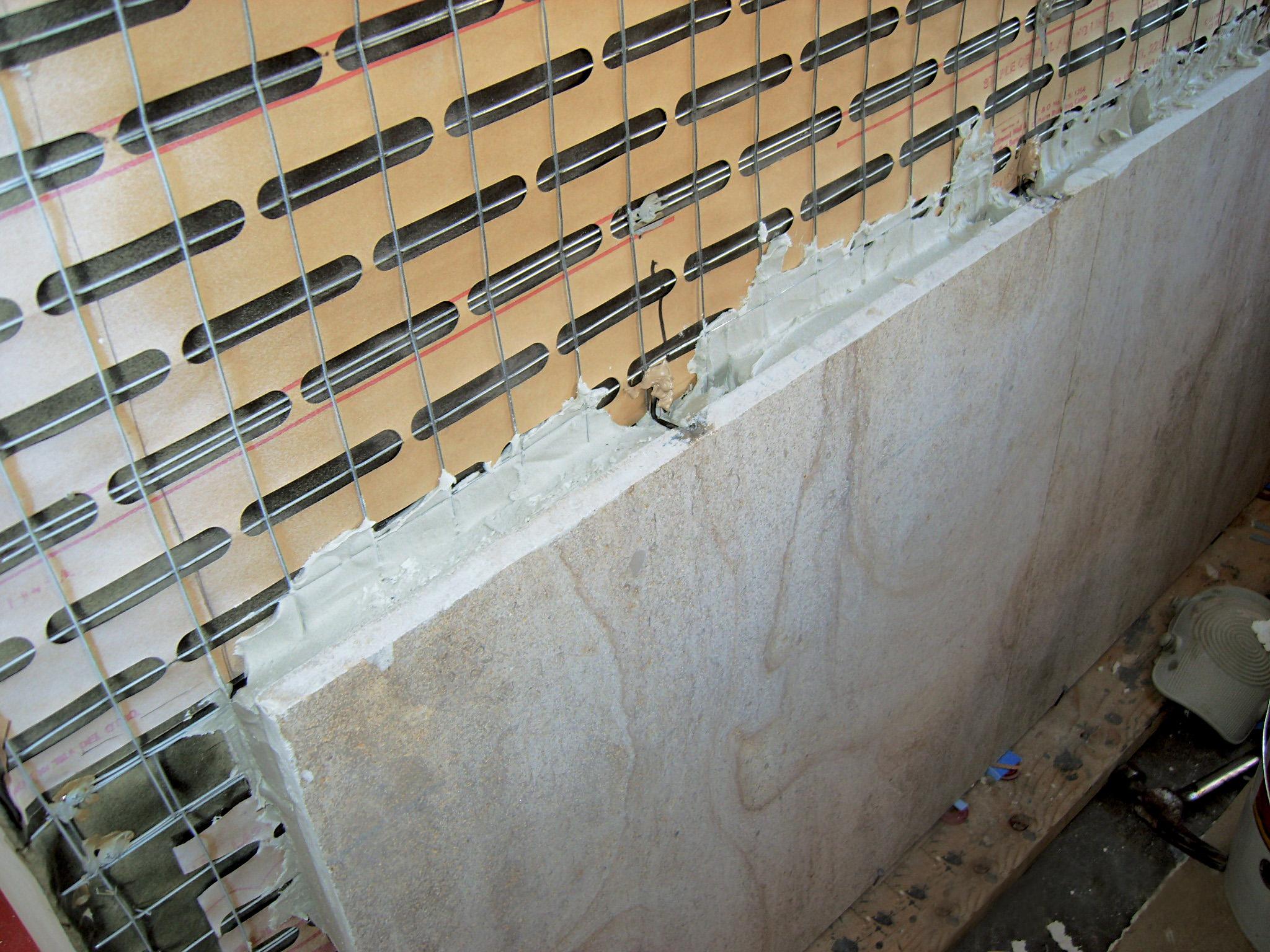 Kireçtaşının binanın dış duvarına tel bağ ankrajlarla mekanik olarak sabitlenmesi.