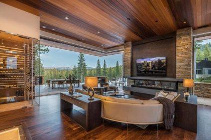 L şeklinde pencereler, ahşap tavanlar ve zeminlerle modern oturma odası tasarımı