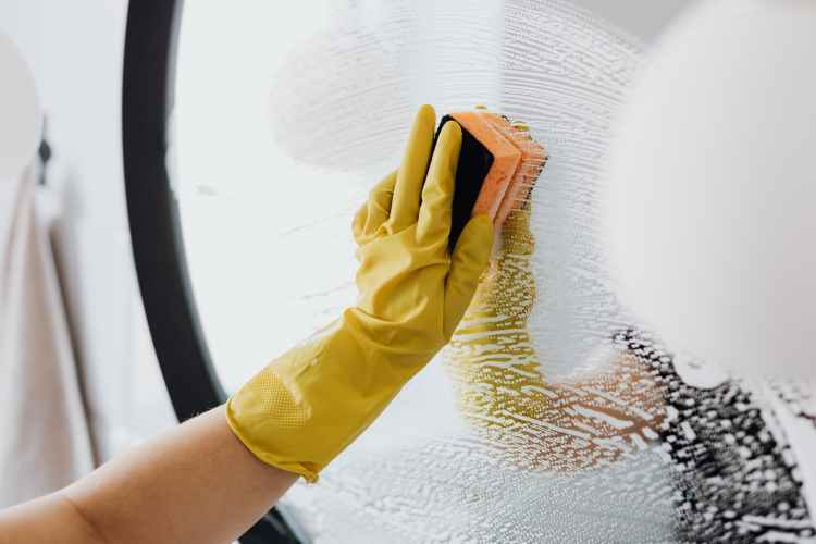 faceless person cleaning mirror with sponge