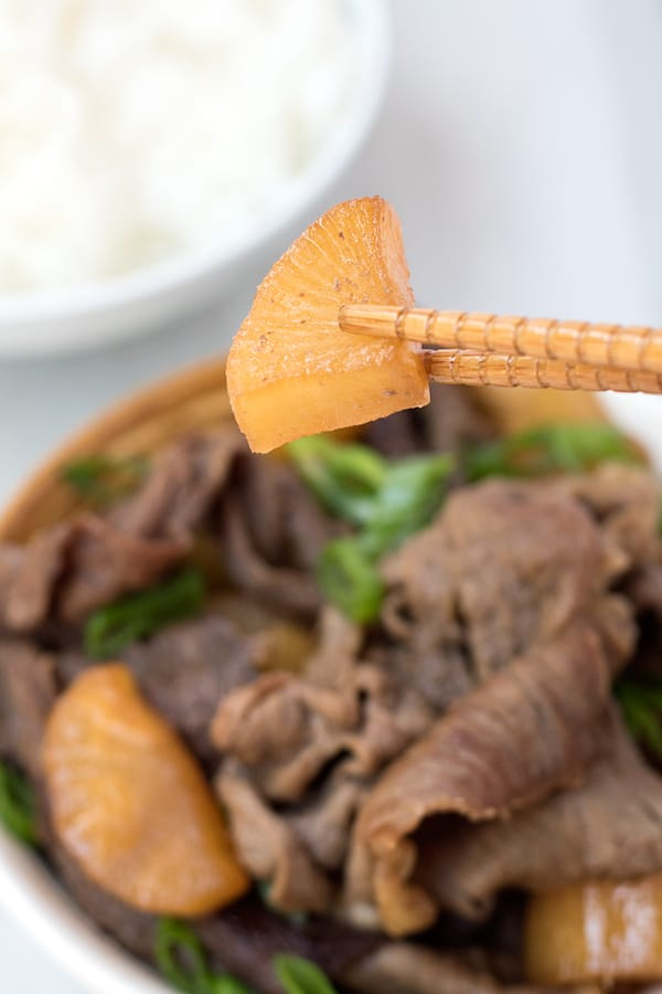 Close up of daikon radish with beef with daikon radish bowl in background.