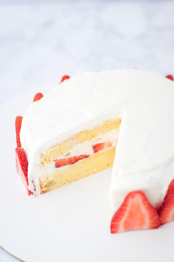 Japanese strawberry shortcake with a slice cut out of it.
