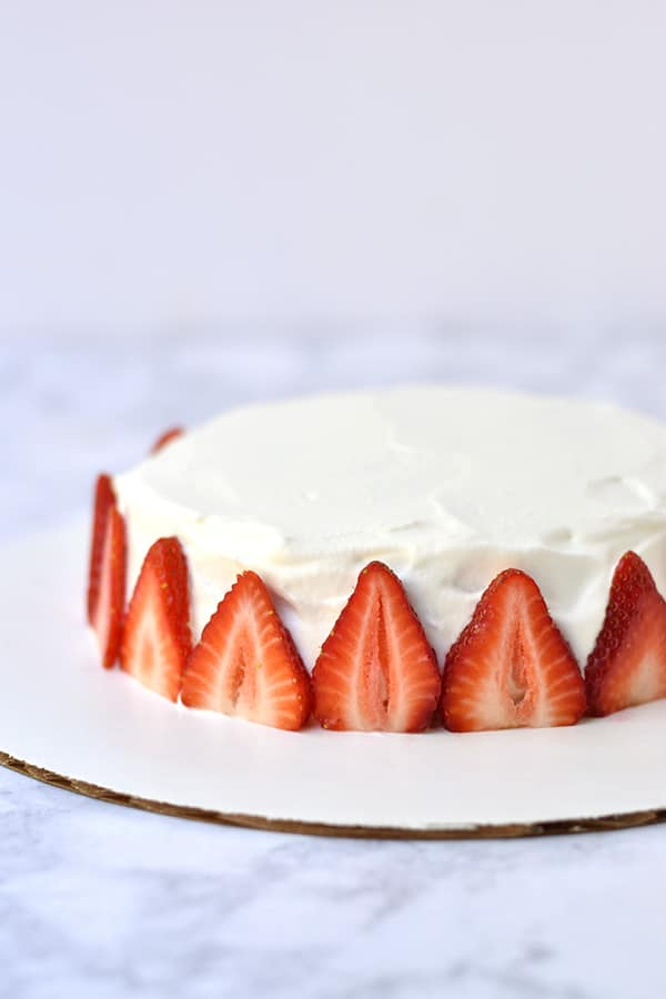 Side view of Japanese strawberry shortcake with strawberry slices around the perimeter.