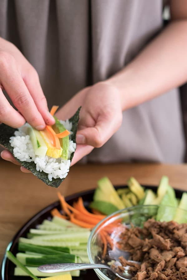 Rolling a sushi hand roll with avocado, carrots, egg, and cucumber.