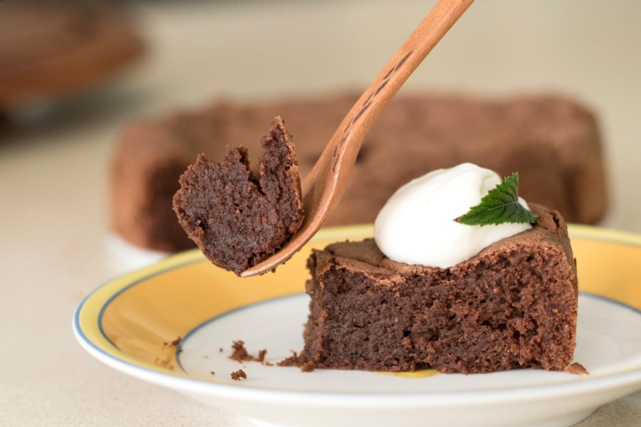 Fork lifting up a piece of gluten free french chocolate cake topped with dollop of whipped cream and mint leaf.
