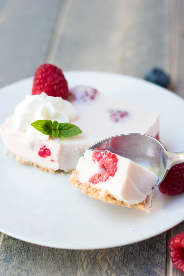 Taking a bite from a raspberry no bake cheesecake bar topped with whipped cream and mint garnish.