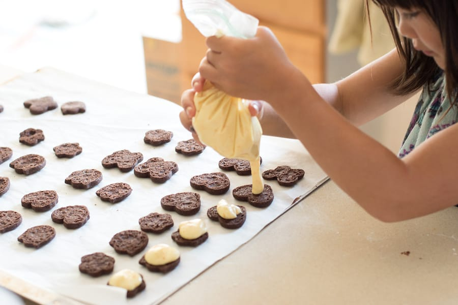 Child piping orange buttercream onto baked chocolate sandwich cookies.