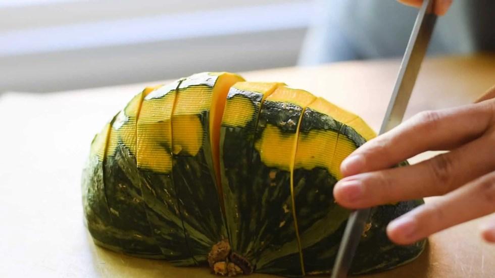 Cutting up a half peeled kabocha squash.