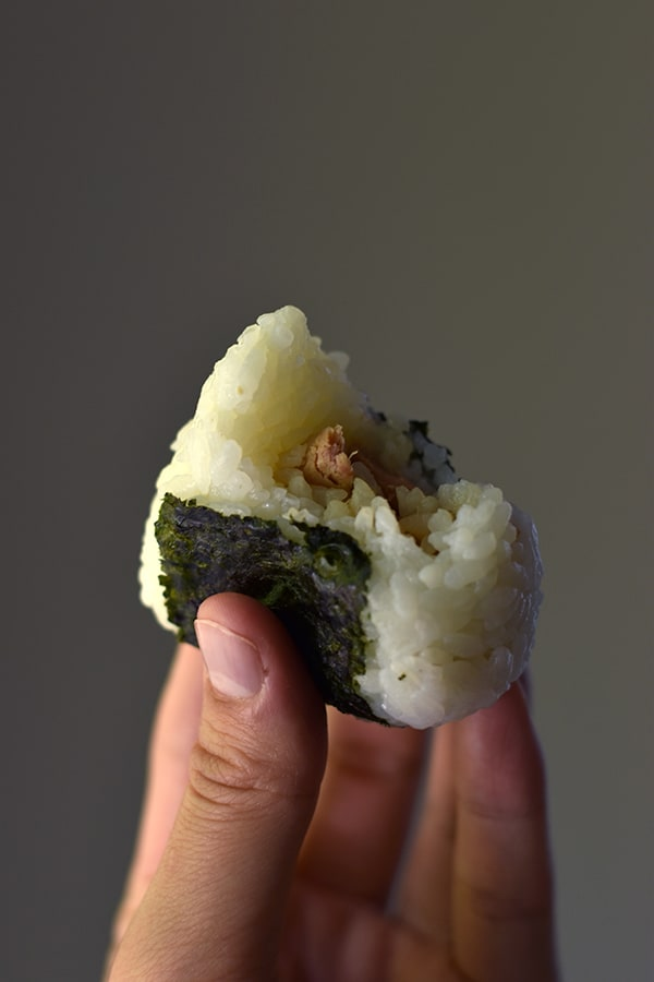 Hand holding a tuna mayo onigiri with a bite taken out of it.