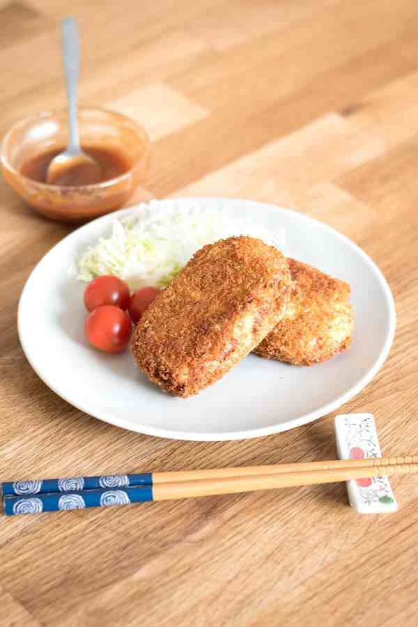 zoomed out picture of korokke dish with tonkatsu sauce in the background.