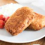 Korokke, or Japanese potato croquettes, served with cherry tomatoes and shredded cabbage.