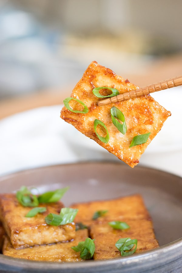 chopsticks holding soy sauce and butter glazed tofu with green onion garnish.