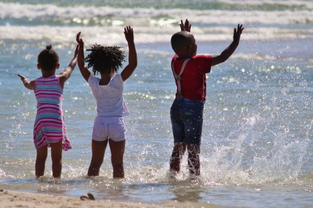 three black children playing in the ocean