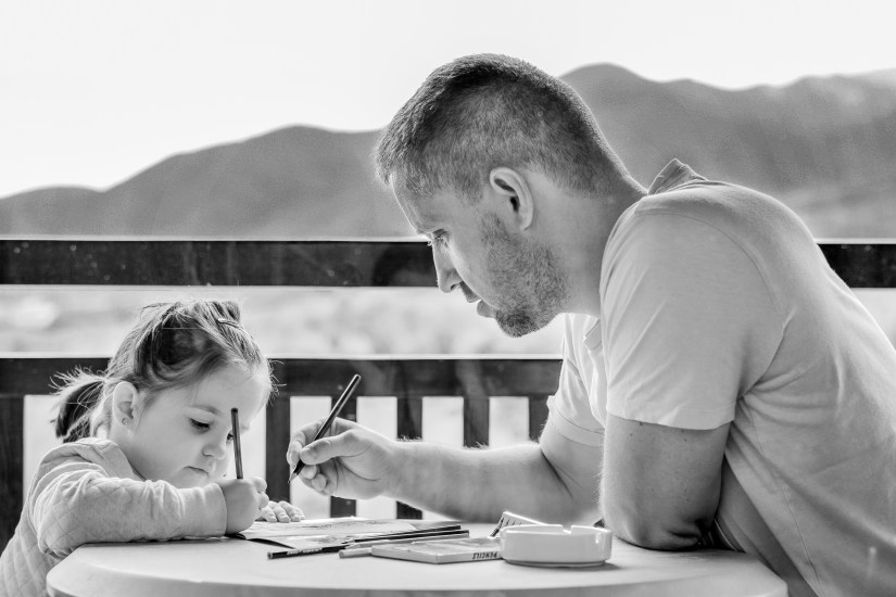 photo of man with his toddler coloring together