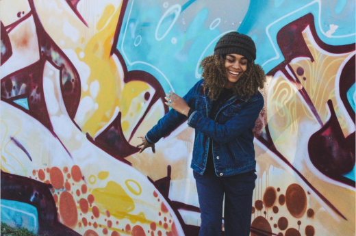 photo of color, graffiti, curly hair, smiling, happy, mural, african american