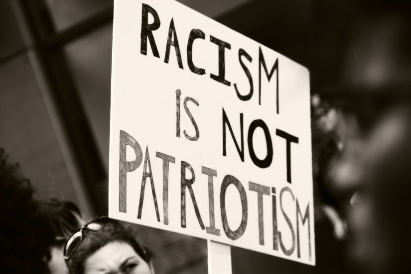 "protest sign saying ""racism os not patriotism"""