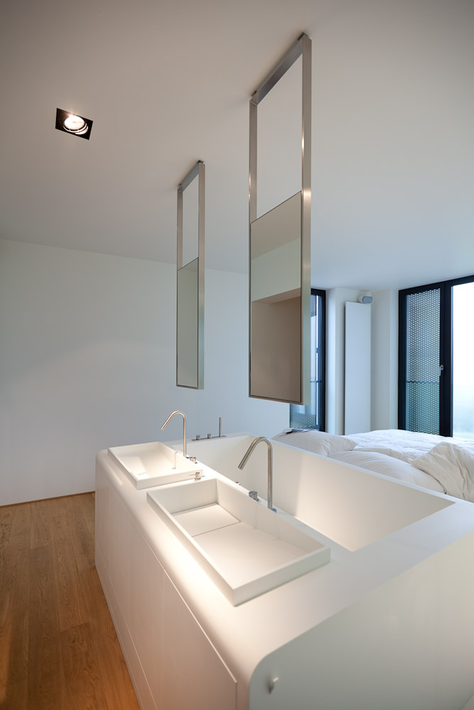 bed attached to a bathtub and two sinks