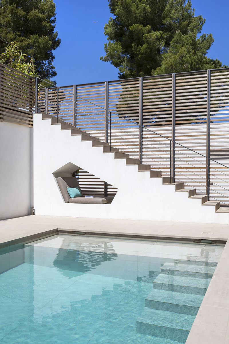 Este rincón asiento incorporado está escondido debajo de la escalera por esta piscina en una casa en Saint Tropez.