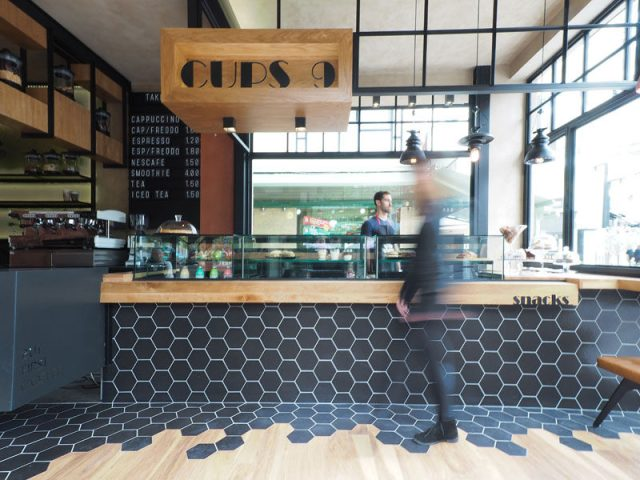 Hexagon Tiles Transition Into Wood Flooring Inside This Cafe In Greece