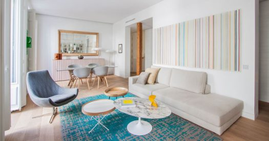 In this modern apartment, the living room and dining room share the open floor plan, while a large mirror on the wall makes the room appear larger than it is. Pops of color in the decor, rug and artwork, help to brighten the space.