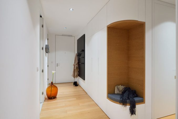 This entryway in a modern apartment has a small section of cabinets, however instead of the cabinets wrapping around the corner, the designers removed a section included a small seat with a cushion surrounded by wood, making it the ideal place to put your shoes on.