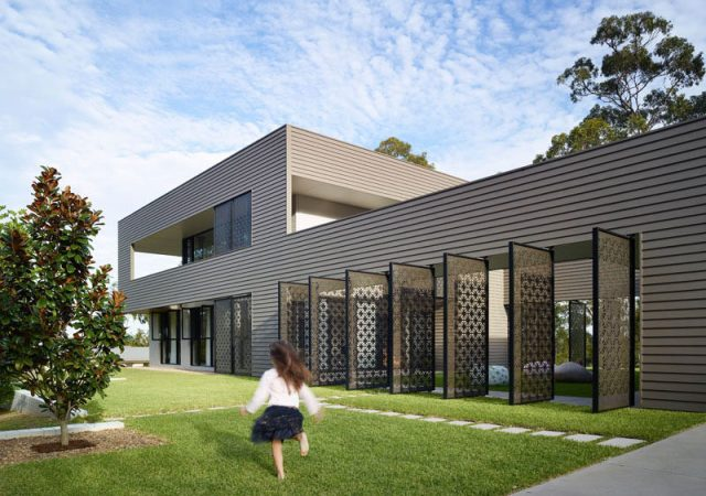Jamison Architects have designed this Australian house that features two pavilions connected by a grassy courtyard and decorative laser cut screens.