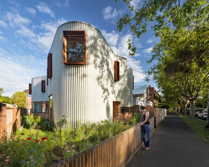 This modern house is covered in a custom made zig-zag metal facade that creates a continuous curving appearance, that sits on top of reclaimed brick and is broken up by rusted steel hoods around the windows.