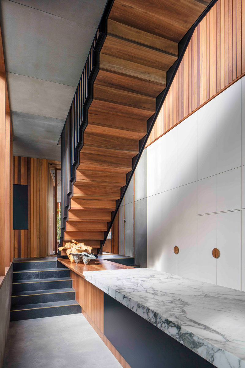 In this modern house, there are small steps that lead to the main living and dining area. A custom wood counter that meets the top of the steps is connected to the countertop on the kitchen island.