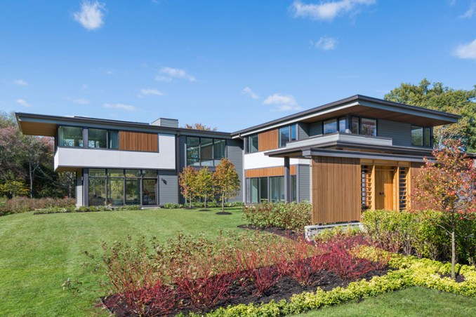 This modern house is on a blueberry farm and features wood accents, floor-to-ceiling windows, and a bright and airy interior.